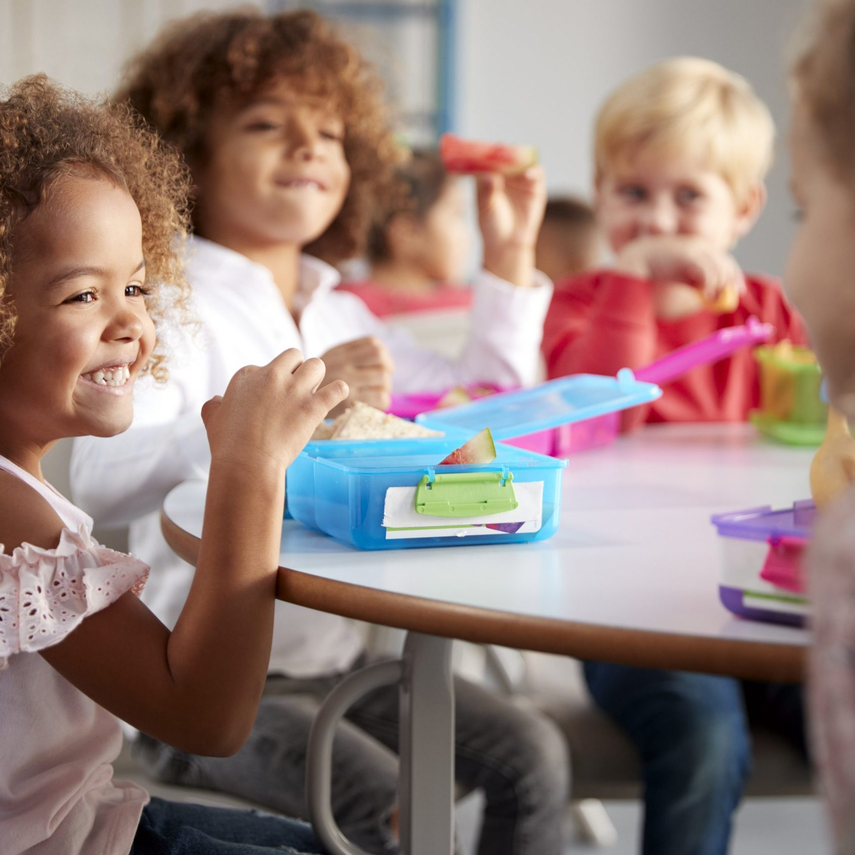 Close up of smiling young children sitting at a table eating their packed lunches together at infant school, selective focus